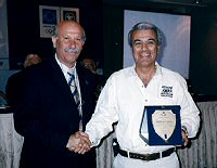 Evaggelos Papapostolou, Technical Director of the Athens Classic Marathon, presenting Paul Samaras with an award for promoting the event.